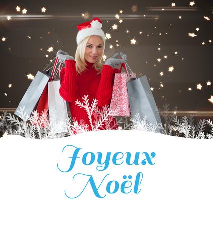 joyeux: happy festive blonde with shopping bags against joyeux noel Stock Photo