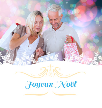 admiring: happy couple with shopping bags against Christmas greeting card Stock Photo