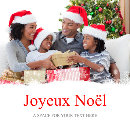 joyeux: Family celebrating Christmas at home against joyeux noel Stock Photo