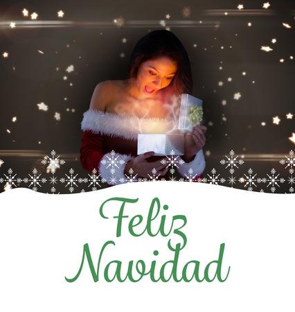 opening gift: sexy santa girl opening gift against feliz navidad Stock Photo