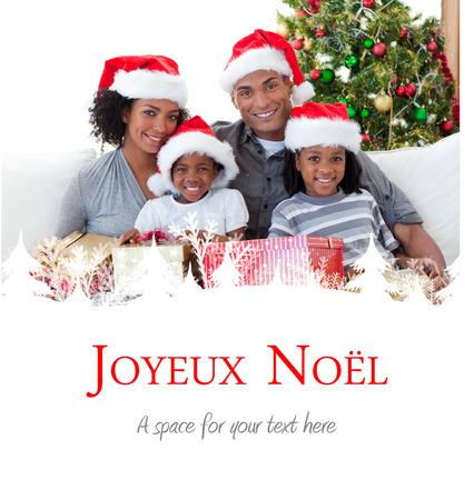 joyeux: Family holding Christmas presents against joyeux noel