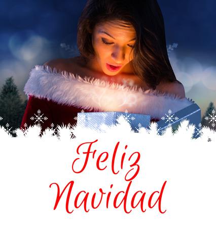 sexy santa girl: sexy santa girl opening gift against feliz navidad Stock Photo