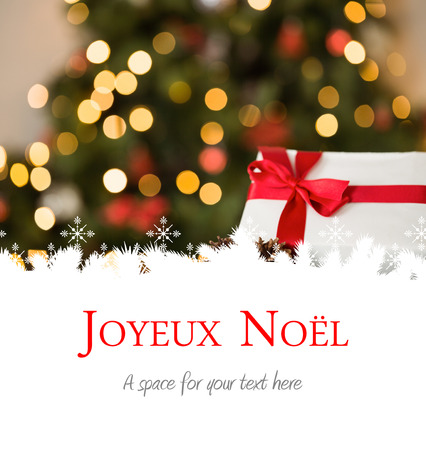 Joyeux noel against focus on christmas gift and pine cone
