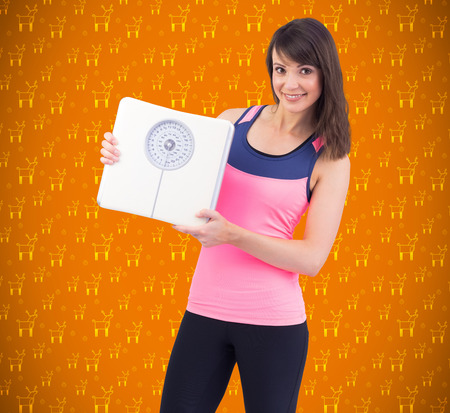 weighing scales: Smiling woman holding weighing scales against orange vignette Stock Photo