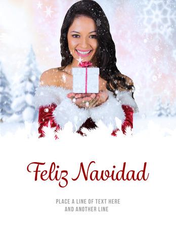 feliz: pretty girl in santa outfit holding gift against feliz navidad
