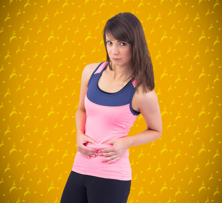 pinching: Festive fit brunette pinching her stomach against yellow background with vignette