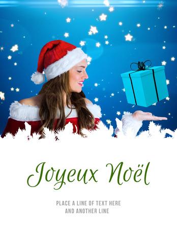 joyeux: pretty girl in santa costume holding hand out against joyeux noel