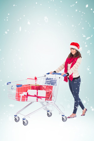 shopping trolley: Brunette in santa hat with shopping trolley against blue vignette Stock Photo