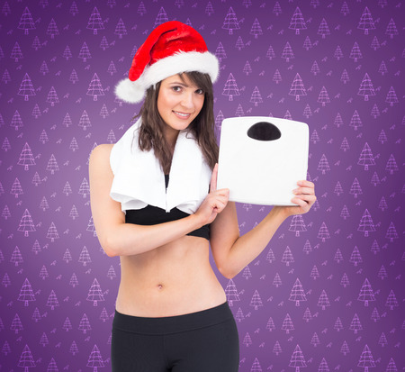 weighing scales: Festive fit brunette holding weighing scales against purple vignette