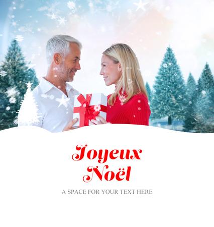joyeux: loving couple with gift against joyeux noel