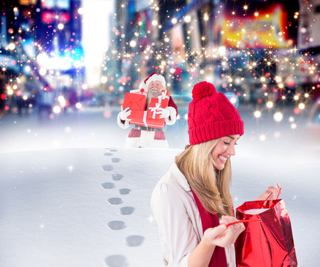 adult footprint: Happy blonde opening gift bag  against santa delivering gifts in city