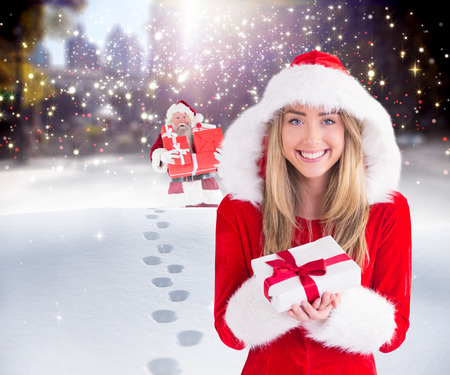 adult footprint: Sexy santa girl holding gift against santa delivering gifts in city Stock Photo