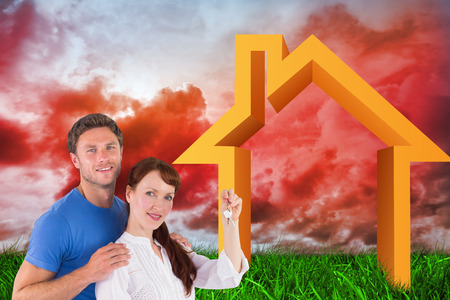 cloudy home: Couple holding keys to home against green grass under red cloudy sky