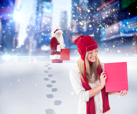 adult footprint: Pretty blonde showing red poster against santa delivering gifts in city