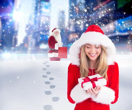 pere noel sexy: Sexy Santa fille tenant cadeau contre Santa livraison des cadeaux dans la ville Banque d'images