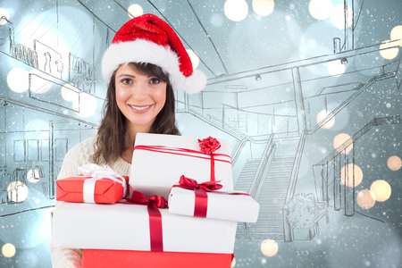 wearing santa hat: Attractive woman wearing santa hat with gifts against white glowing dots on blue Stock Photo