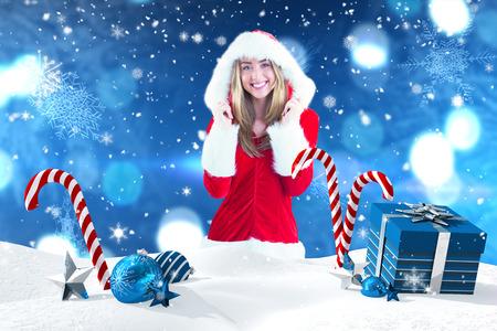 pere noel sexy: Jolie Santa Girl souriant � la cam�ra contre la sc�ne de No�l avec des cadeaux et des cannes de bonbon