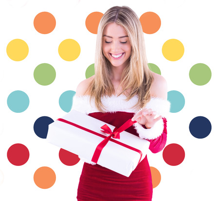 opening gift: Pretty santa girl opening gift against colorful polka dot pattern