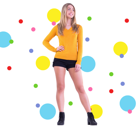 hot pants: Stylish blonde smiling with hand on hip against dot pattern