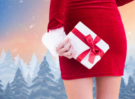 gift behind back: Sexy santa girl holding gift behind back against snow falling on fir tree forest