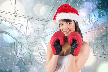 strong women: Festive brunette with boxing gloves against light glowing dots on blue