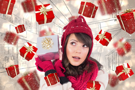 Young woman shaking her gift in order to guess what it is against light glowing dots design pattern Stock Photo