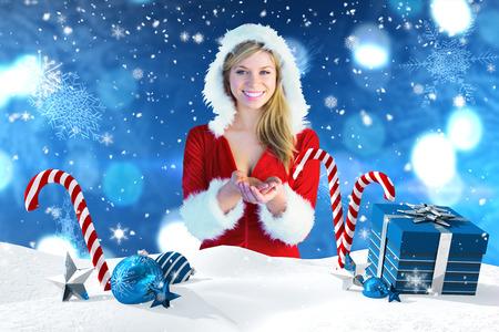 pere noel sexy: Jolie fille tenant par la main dans Santa tenue contre la scène de Noël avec des cadeaux et des cannes de bonbon Banque d'images