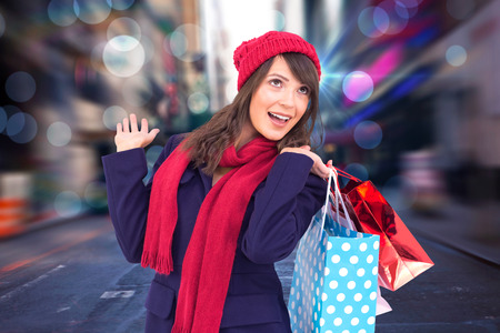 Happy brunette in winter clothes holding shopping bags against blurry new york street Stock Photo