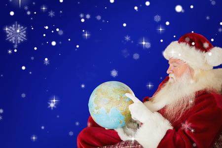 pere noel: P�re No�l pointant vers globe sur fond rouge Banque d'images
