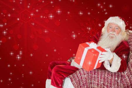 pere noel: P�re No�l offrant un cadeau rouge sur fond rouge Banque d'images