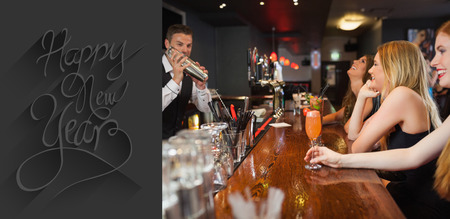 shaking out: Handsome bartender making cocktails for beautiful women against classy new year greeting