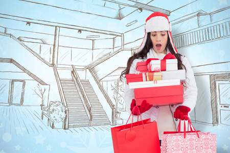 winter wallpaper: Surprised brunette in winter clothes holding many gifts and shopping bags against snowflake wallpaper pattern