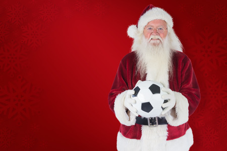 classic santa: Santa holds a classic football  against red background