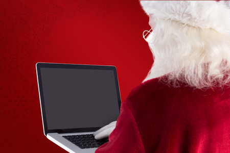 home trainer: Santa Claus uses a laptop against red background
