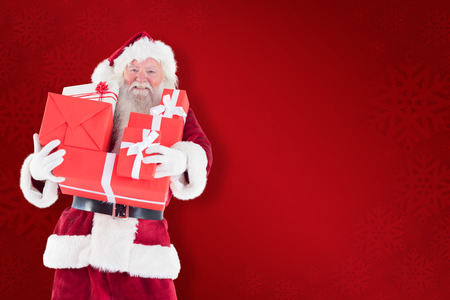 lean back: Santa carries a few presents against red background