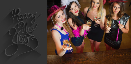 hen party: Happy gorgeous women holding flutes of champagne having hen party against classy new year greeting