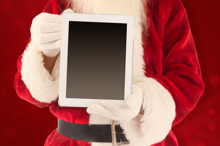 lean back: Santa claus showing tablet pc against red background Stock Photo
