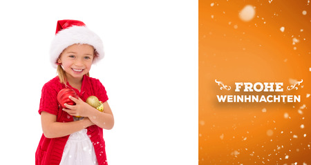 wearing santa hat: Cute little girl wearing santa hat holding baubles against orange vignette Stock Photo