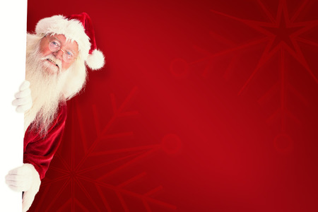 peep out: Santa looks out behind a wall against red background