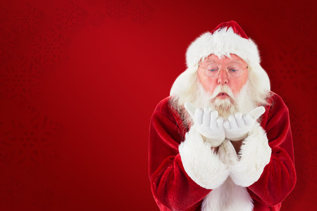 clear away: Santa Claus blows something away against red background