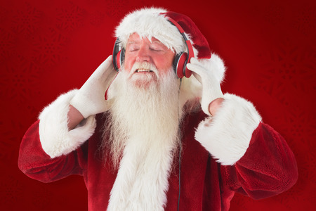 home trainer: Santa Claus enjoys some music against red background Stock Photo