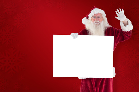 home trainer: Santa holds a sign and is waving against red background Stock Photo