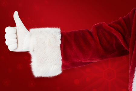 lean back: Father Christmas gives a thumb up against red background