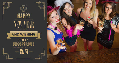 hen party: Happy gorgeous women holding flutes of champagne having hen party against art deco new year greeting Stock Photo