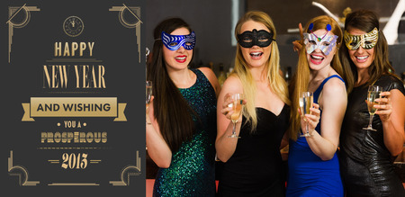 hedonistic: Laughing friends wearing masks holding champagne glasses against art deco new year greeting