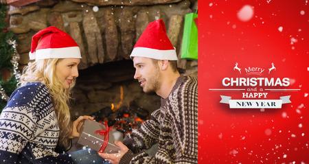 gifting: Hombre regalar mujer delante de la chimenea encendida durante la Navidad contra la vi�eta roja