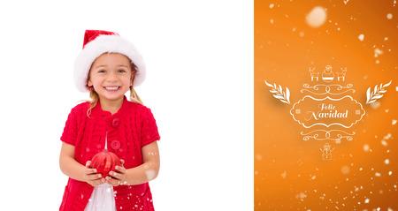 wearing santa hat: Cute little girl wearing santa hat holding bauble against orange vignette