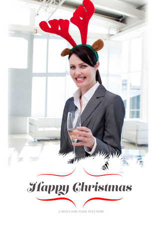 novelty: Smiling businesswoman with a novelty Christmas hat toasting with Champagne  against border