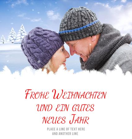 weihnachten: mature winter couple against frohe weihnachten message Stock Photo