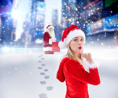 adult footprint: Festive blonde blowing a kiss against santa delivering gifts in city